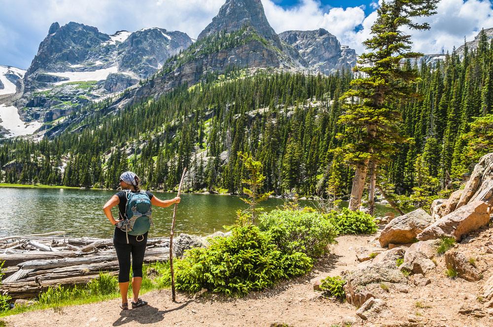 A woman standing beside a mountain lake near Winter Park Colorado